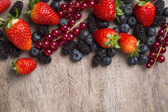 Some Redfruits over a wooden table. Some gooseberries, raspberries, strawberries and blueberries over a wooden table stock photos