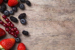 Some Redfruits over a wooden table. Some gooseberries, raspberries, strawberries and blueberries over a wooden table royalty free stock image