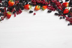 Some Redfruits over a wooden table. Some gooseberries, raspberries, strawberries and blueberries over a wooden table royalty free stock photo