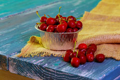 Some ripe Cherries with sparkling Water Drops in small Basket old Wooden Table Stock Photo