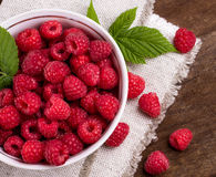 Some ripe and fresh raspberry in white cup. Top view of ripe and fresh raspberry in white cup and some raspberry sprinkled on wooden desk Royalty Free Stock Images