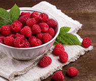 Some ripe and fresh raspberry in white cup. View from above on handful of ripe and fresh raspberry in white cup and some raspberry sprinkled on white wooden desk Stock Photos