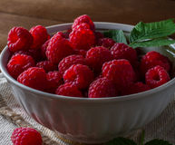 Some ripe and fresh raspberry in white cup. View from above on handful of ripe and fresh raspberry in white cup and some raspberry sprinkled on white wooden desk Royalty Free Stock Photos