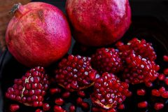 Some ripe juicy red pomegranate fruit on the plate. Punica gran Royalty Free Stock Images