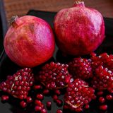 Some ripe juicy red pomegranate fruit on the plate. Punica gran Royalty Free Stock Photos