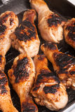 Some roast chicken drumstick on frying pan. Some juicy roast chicken drumstick on frying pan royalty free stock image