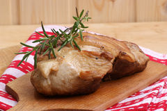 Some roast pork. And rosemary on a timber board Stock Photography