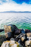 Some rocks in front of nice big lake. With waves. On the other side there are forest, mountains and mild haze. Autumn clouds on blue colored sky stock photo