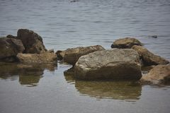 Some rocks. Reflected on the water of the seashore during the day stock images