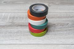Colored insulating tape. Some rolls of insulating tape of various colors on a wooden table stock image