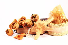 Some romantic objects in retro style. Dried yellow roses on a book, with starfish and some famine objects over white royalty free stock images