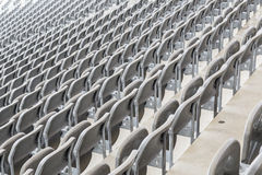 Some rows of gray stadium seats. Shoot from behind stock images