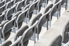 Some rows of gray stadium seats. Shoot from behind stock photography