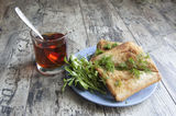 Some sandwiches on the blue plate on the old wooden table. Near glass of tea. Horizontal stock image
