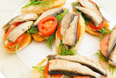 Some sandwiches with sprats on a dish. On white Royalty Free Stock Photos