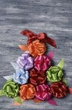 Gift ribbon bows forming a christmas tree. Some satin gift ribbon bows of different colors forming a christmas tree on a gray rustic wooden background, with a Royalty Free Stock Photo