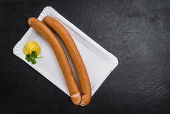 Some Sausages Frankfurter on a dark slate slab. Sausages Frankfurter on a vintage slate slab close-up shot; selective focus Royalty Free Stock Photography