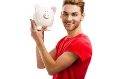 Some savings for my studies. Handsome young holding a piggybank and smiling, isolated over a white background Stock Photo