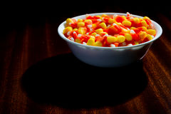 Some scary candy corn. Candy corn in a bowl on a table that is lightly lit stock photo