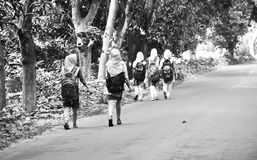School going girls are walking on the street unique photograph. Some of the school going girls are walking on the road with school bags on shoulder isolated royalty free stock photo