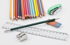 Some school supplies. School supplies with many colored pencils, eraser, sharpener, stapler and plastic ruler Stock Images