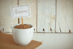 Some sesame seeds in a bowl in the herbalist's. Empty copy space against a wooden background Royalty Free Stock Photos
