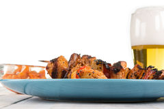 Some shashlik spits on a bluish plate, decorated with a beer in Stock Photography