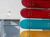 Skateboard decks hanging in front of a building with some graffi royalty free stock photography