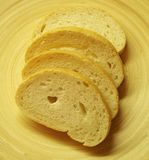 Some sliced bread on a plate. Some sliced bread on a wooden plate royalty free stock photo