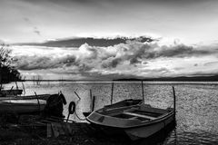 Small fishing boat on a lake. Some small fishing boat on a lake, beneath a cloudy, moody sky royalty free stock photos