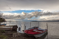 Some small fishing boat on a lake, beneath a cloudy, moody sky,. With some blue openings Royalty Free Stock Photo