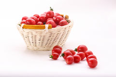 Some small tomatoes isolated on white background in the basket.  Royalty Free Stock Photo