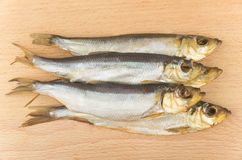 Some smoked fish on wooden board. Some smoked fish on board of beech Royalty Free Stock Images