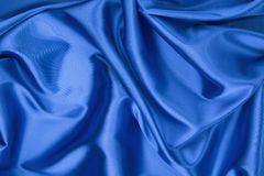 Some soft folds of blue silk cloth. Whole background royalty free stock photography