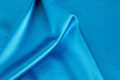 Some soft folds of light blue silk cloth. Whole background royalty free stock images