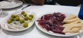 Some spanish tapas such as serrano ham. And olives Stock Photo