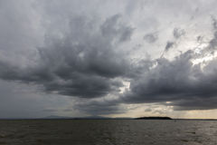 Some spectacular and menacing clouds over a lake, with a distant. Island in the background Royalty Free Stock Image