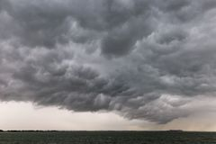 Some spectacular and menacing clouds over a lake, with a distant Royalty Free Stock Photo