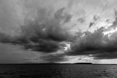 Some spectacular and menacing clouds over a lake, with a distant. Island in the background Stock Image