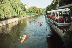Some sport boats Kayaks floating on river under green trees. BERLIN, GERMANY - SEPT 1, 2015: Some sport boats Kayaks floating on river under green trees on Royalty Free Stock Photo