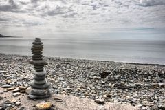 Some stones balancing on top of each to make a tower on a beach. Stones balancing on top of each to make a tower on a beach Stock Image