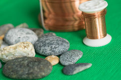 Some stones and copper wire. On a textile background Royalty Free Stock Photography