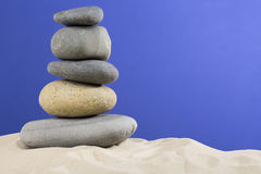 Some stones on each other with nice sand against blue background.  stock image
