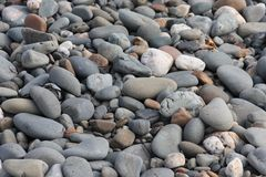 Some stones and rocks on a sandy beach background Royalty Free Stock Photos