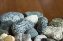 Some stones scattered on a wooden surface. Close up Royalty Free Stock Photo