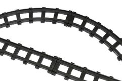 Some straight and curved toy train track pieces. A photo taken on some black colored straight and curved toy train track pieces against a white backdrop stock image