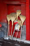 Chinese straw brooms. Some straw brooms leaning against a red door royalty free stock photos