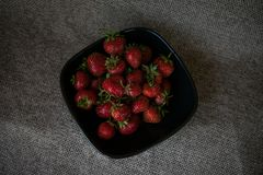 Some strawberries in a black plate Royalty Free Stock Photos