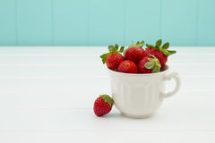 Some strawberries in a cup. A white wooden table and a turquoise background Stock Image