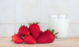 Some strawberries and a glass of milk. A composition with some strawberries and a glass of fresh milk on a wooden chopping board, inside a kitchen, landscape cut royalty free stock images